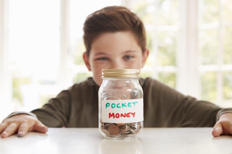 Denaro per piccole spese di risparmio del ragazzo in barattolo di vetro a casa immagini stock
