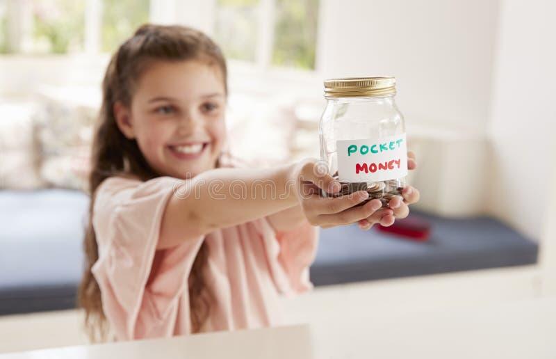 Denaro per piccole spese di risparmio della ragazza in barattolo di vetro a casa immagine stock libera da diritti