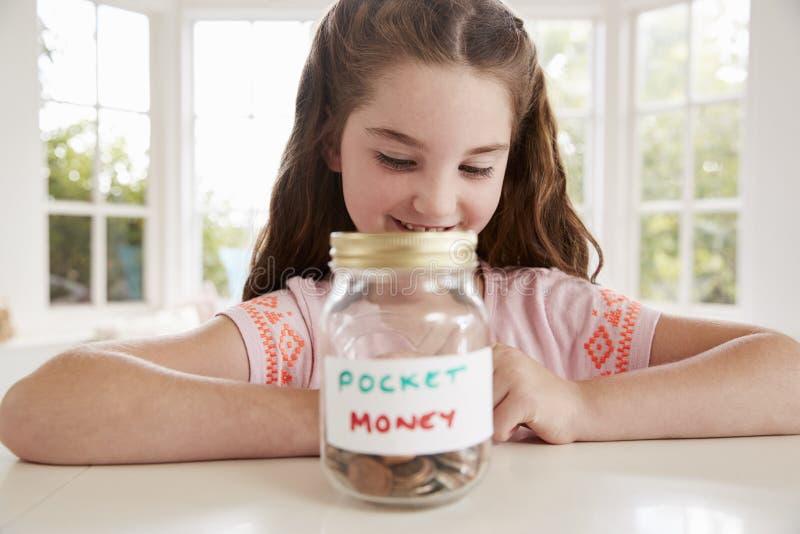 Denaro per piccole spese di risparmio della ragazza in barattolo di vetro a casa fotografia stock libera da diritti