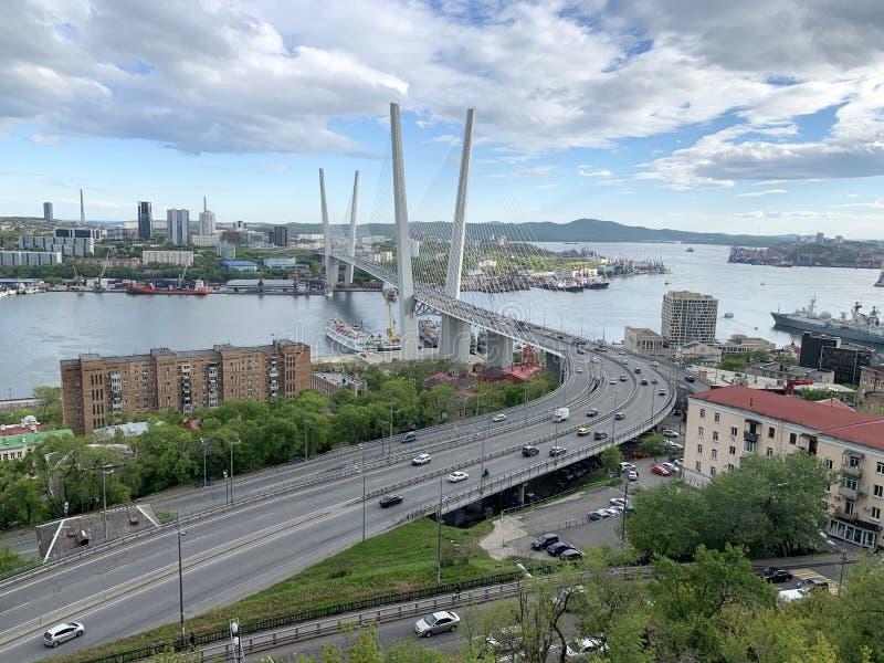 denblivna bron över Zolotoy Rog Golden den horn- fjärden och Churkin udde i Vladivostok i kan i aftonen, Ryssland royaltyfria foton