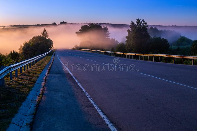Dence early morning fog in wold at summer highway near river with guard rails. Early morning fog in wold at summer highway near river with guard rails stock photo