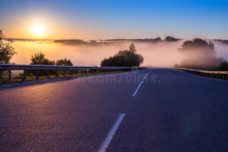 Dence early morning fog in wold at summer highway near river with guard rails. Early morning fog in wold at summer highway near river with guard rails royalty free stock photo