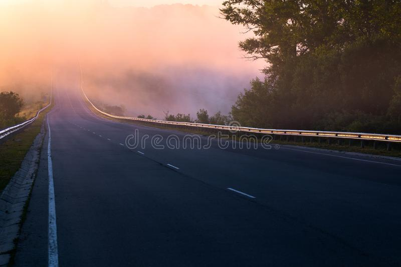 Dence early morning fog in wold at summer highway near river with guard rails. Early morning fog in wold at summer highway near river with guard rails stock image