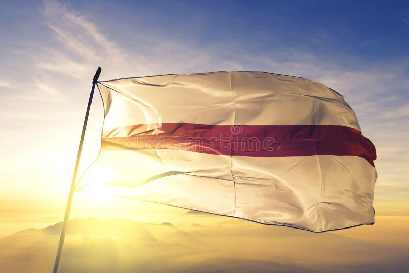 Dendermonde of East Flanders of Belgium flag waving on the top sunrise mist fog. Dendermonde of East Flanders of Belgium flag textile cloth fabric waving on the stock photos