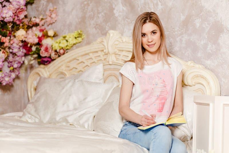 dengamla gulliga Caucasian kvinnan som sitter på sängen i morgonen och, skriver i dagboken royaltyfria bilder