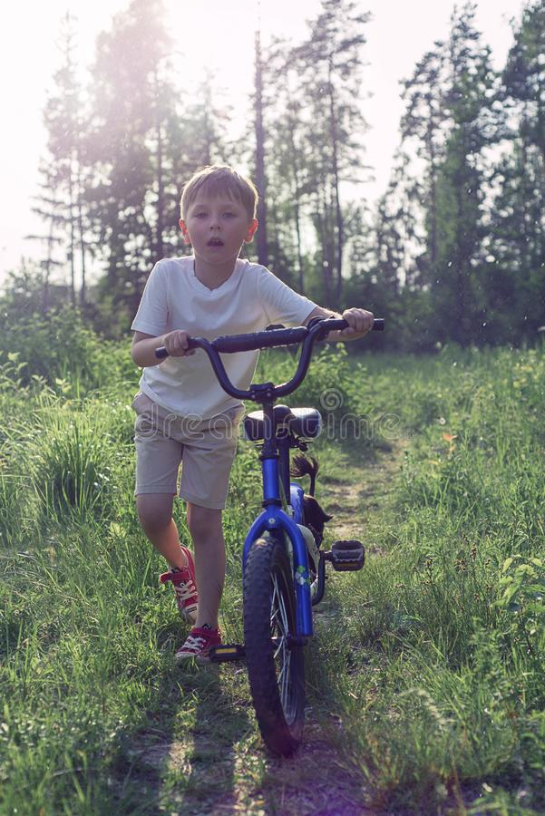 dengamla pojken som rider en cykel i, parkerar arkivbild