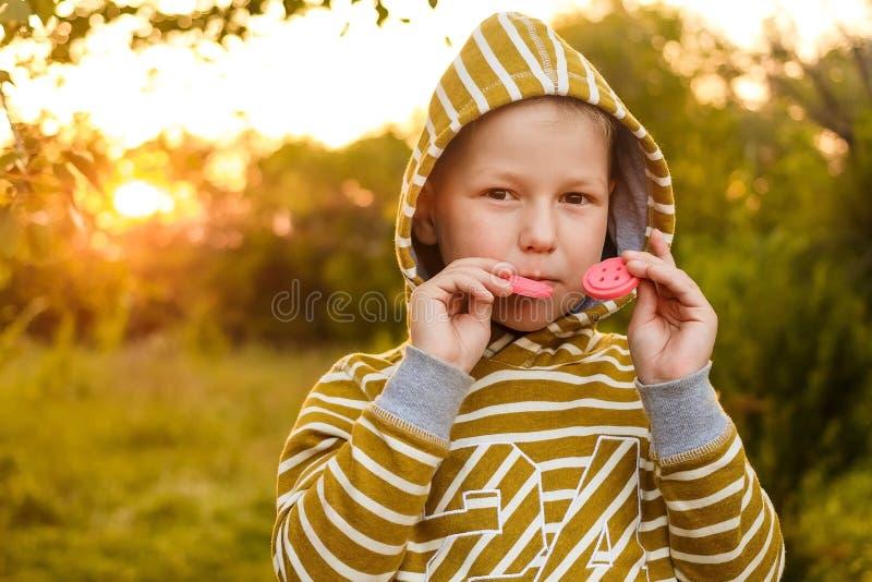 dengamla ungen i en gul hoodie biter kakor i sommaren arkivfoto