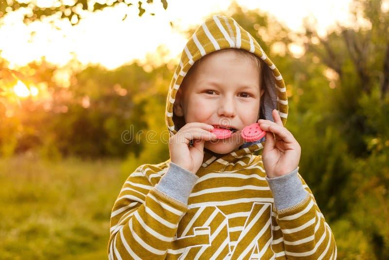 dengamla ungen i en gul hoodie biter kakor i sommaren arkivbild