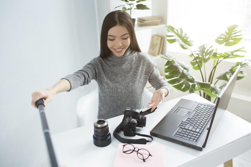denhaired flickan sitter på tabellen och strömmar en video Hon visar henne utrustning för photoshoots till henne royaltyfri bild