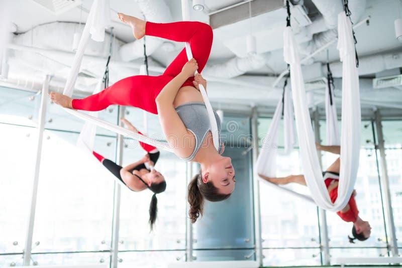 denhaired instruktören i röd damasker som visar trevlig flyg- yoga, poserar royaltyfria foton