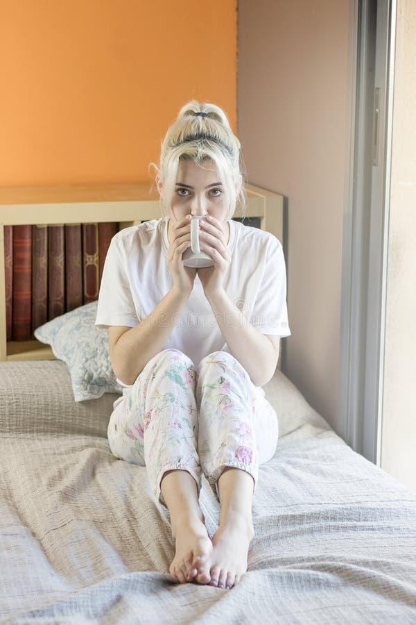 denhaired nätta damen i pyjamas dricker hennes morgoncof arkivbild