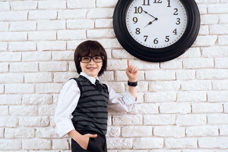 Denhaired pojken står vid den vita väggen i en dräkt Han pekar på väggklockan En liten framtida affärsman arkivfoton