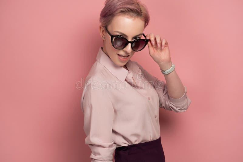 denhaired unga kvinnan ser till och med hennes solglasögon på kameran, rosa bakgrund royaltyfri foto