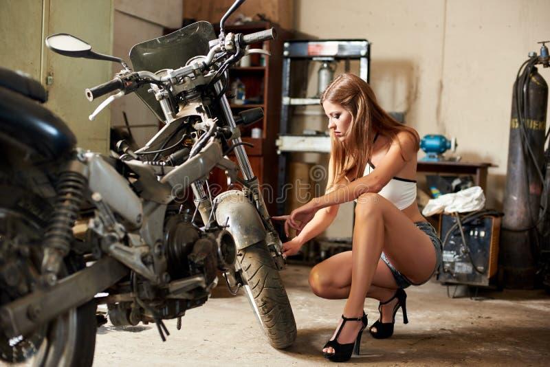 Denheeled brännande brunetten i korta kortslutningar och sitter nära motorcykeln royaltyfri bild