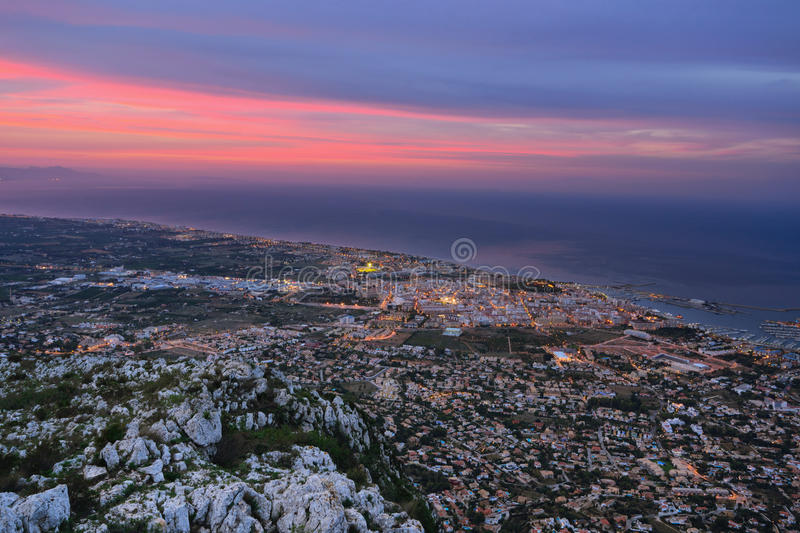 Denia in twilight. View of seaside part of Denia and sea port in twilight. Spain royalty free stock images