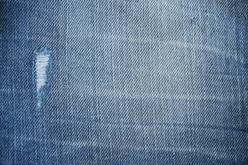Denim background. Blue denim texture, dark jeans with hole royalty free stock image