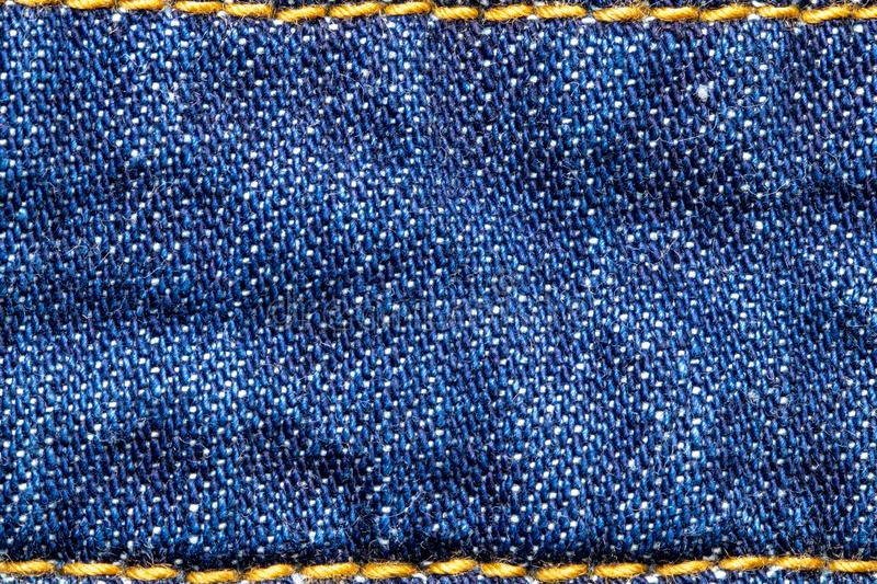 Denim background texture. Close-up of blue jeans fabric frame with simple yellow seam at the top and bottom. Large copy space for. Design. Beautiful backdrop stock image
