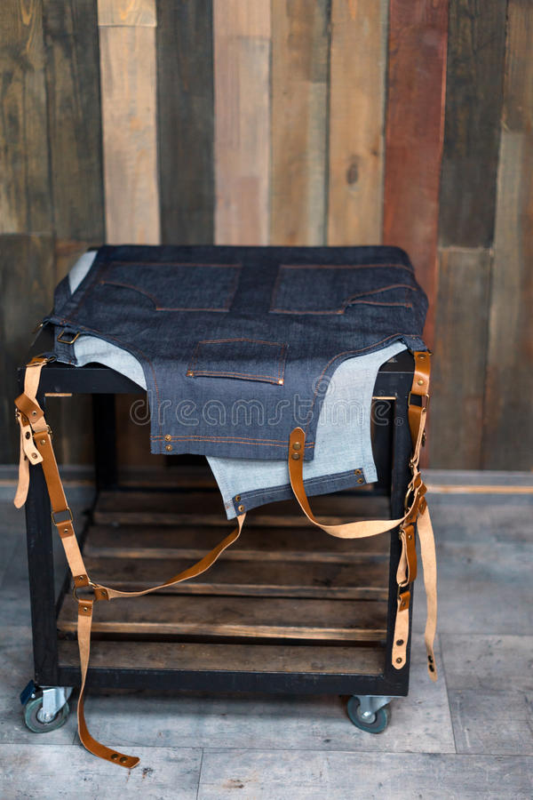 Denim bartender apron with leather straps on the table. Wooden background, free space for text. royalty free stock image