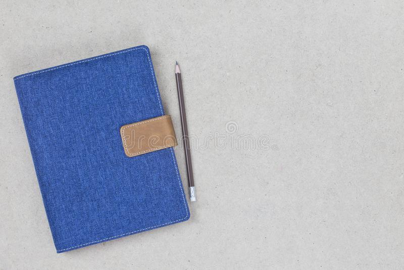 Denim blu della copertura del taccuino con l'etichetta vuota su fondo di legno immagine stock