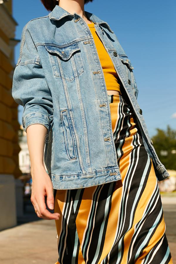 Denim blue jacket on the girl in the image in yellow colors. Street style. Fashion royalty free stock photography