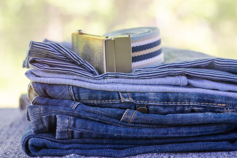 Denim blue jeans stack on a blurred natural background. Accessory belt denim royalty free stock photography