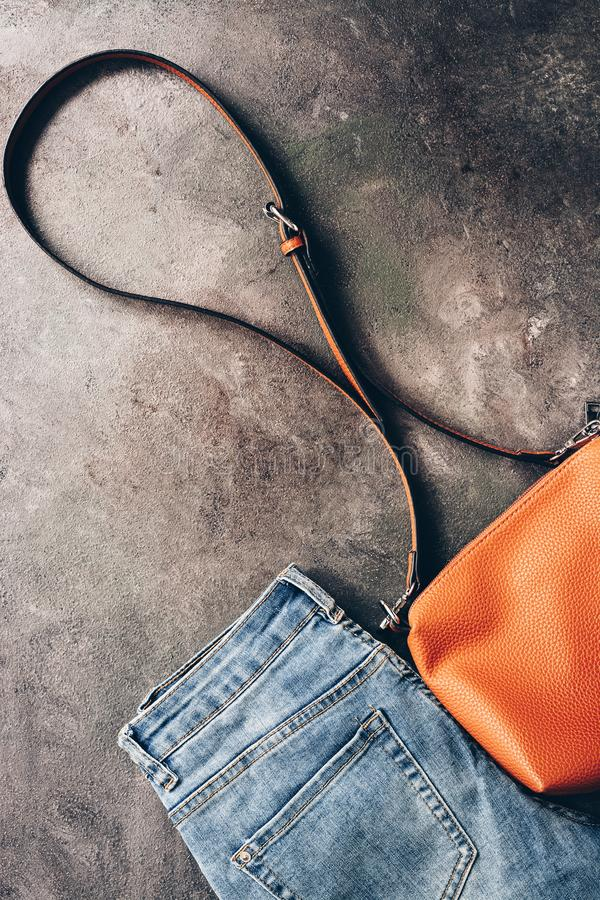 Denim blue jeans stacked and brown leather cross body bag on a dark textured rustic background. Fashionable casual outfit. Top royalty free stock photo
