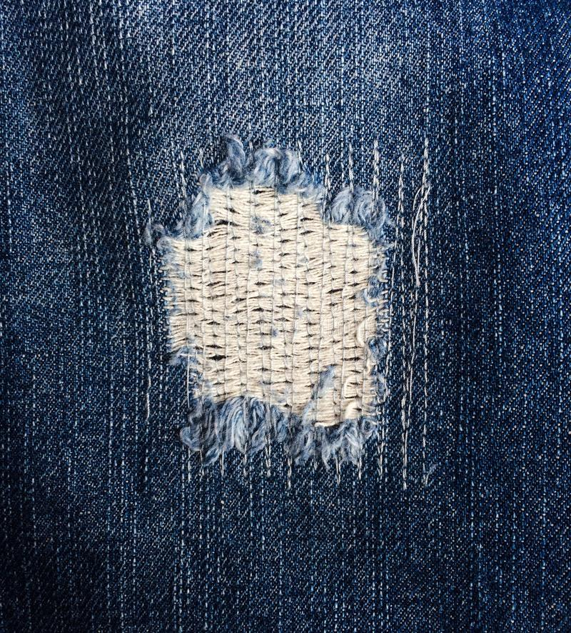 Denim Hole Patch. A zigzag stitched patch on closing a hole in denim fabric. This is an intentional style design of contemporary jeans royalty free stock images