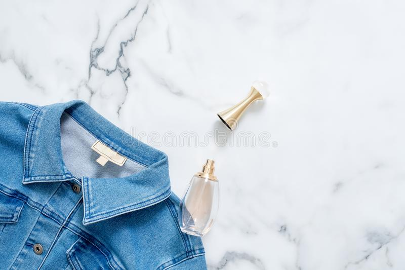 Denim jacket and bottle of perfume on marble background. Flat lay design composition with feminine clothing and accessories. Beaut. Y blogger, trendy hipster stock photo
