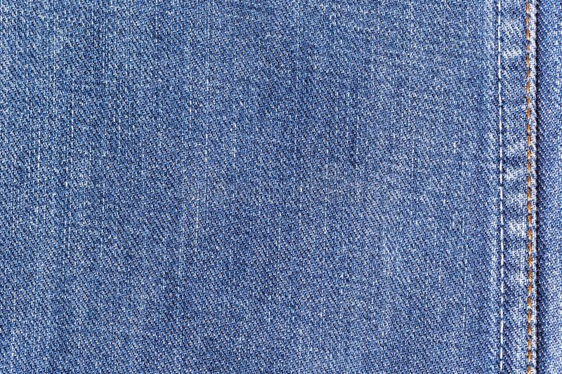 Denim jeans fabric texture background with seam for clothing, fashion design and industrial construction concept.  royalty free stock images