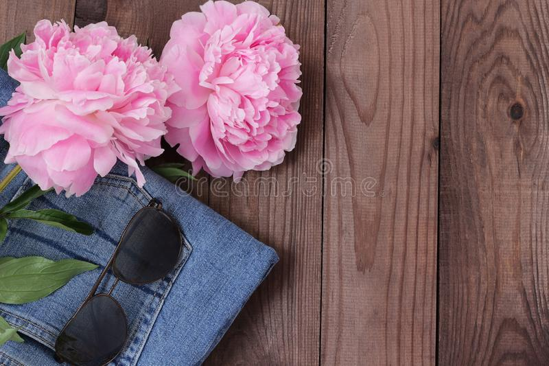 Denim outfit with sun glasses and flowers flatlay royalty free stock images