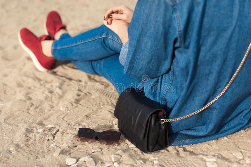 Denim outfit fashion details. Back view stylish woman with red glitter manicure in navy jeans holding sunglasses and leather small stock image