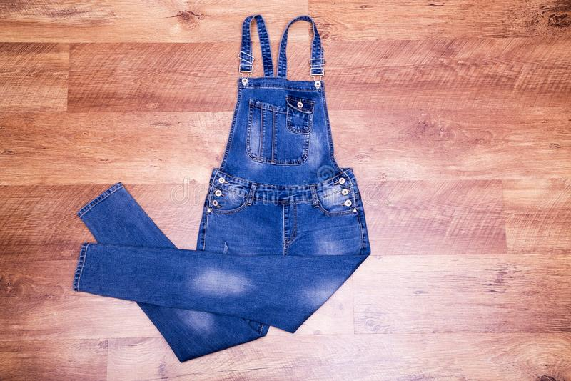 Denim overalls on the floor. Free space near women`s overalls royalty free stock photography