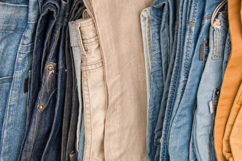 Denim pants folded in a pile on the counter, trade of men`s trousers. 2 royalty free stock image