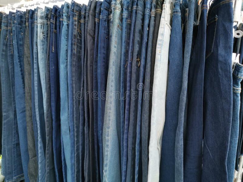 Denim pants hang on rack royalty free stock images