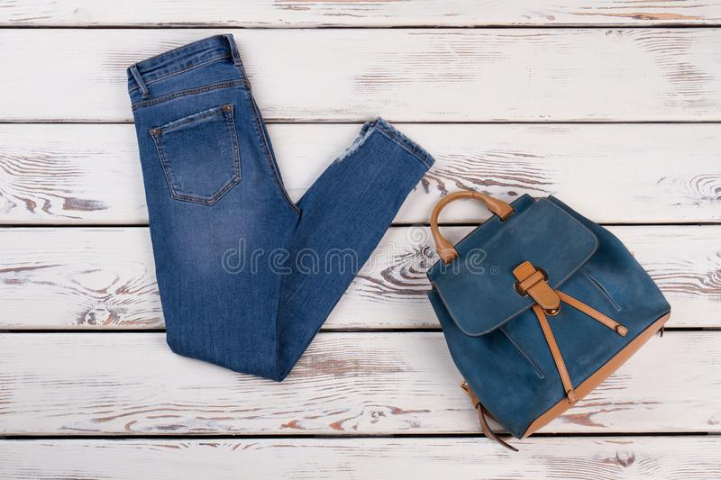 Denim pants and leather backpack. Old wooden display at store. Details of hipster style for girls royalty free stock image