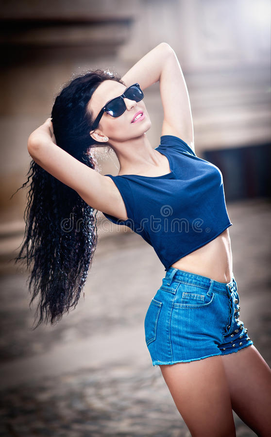 Denim shorts and sunglasses in urban background stock images