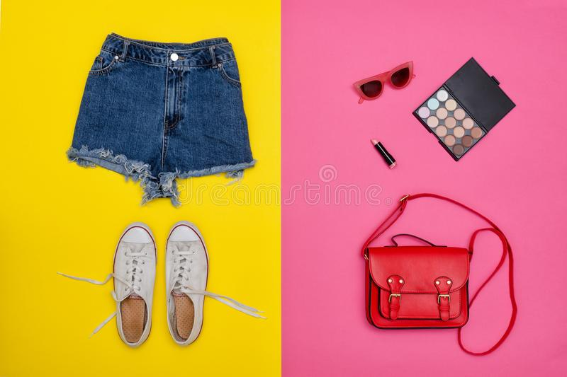 Denim shorts, white sneakers, red handbag, cosmetics. Bright yellow and pink background. Fashionable concept.  royalty free stock photography
