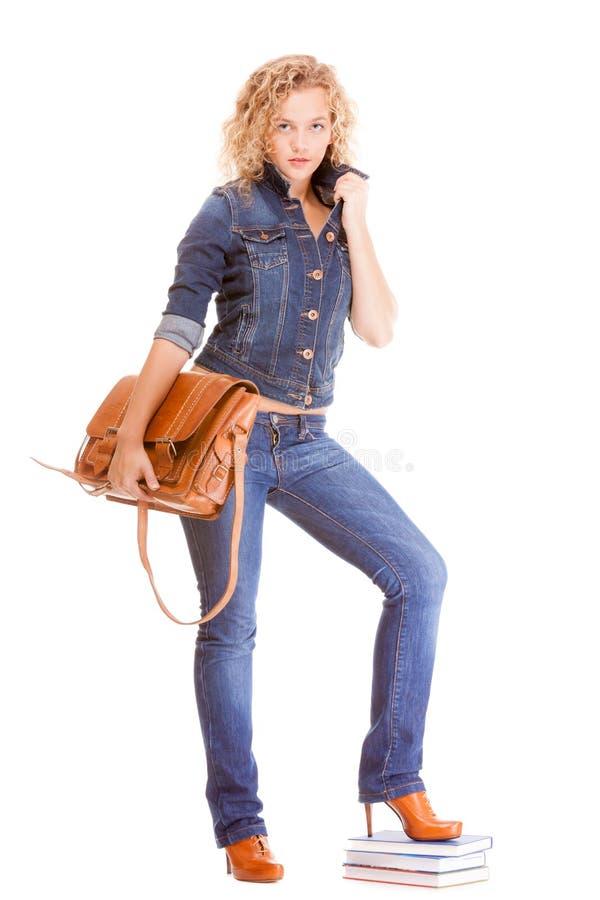 Denimmode. Studentenmädchen in voller Länge in den Blue Jeans-Taschenbüchern lizenzfreie stockfotografie