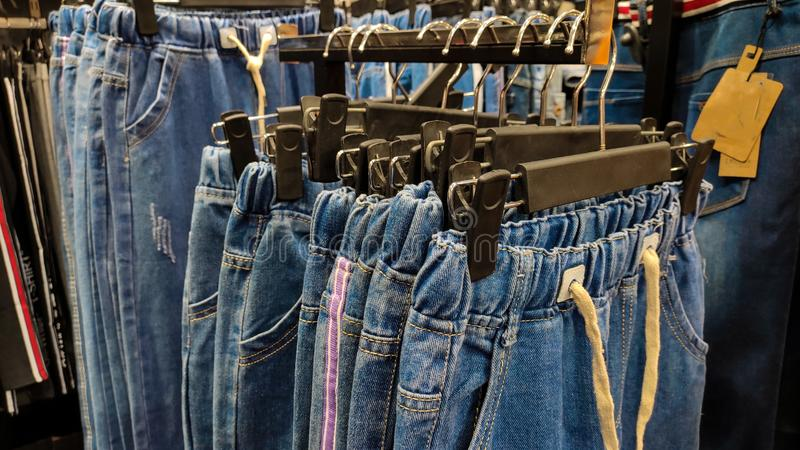 Denims hanging on hangers in a clothing store ready to be sold. Blue denim made of jeans hanging on hangers in a row inside a clothing store ready to be sold royalty free stock images