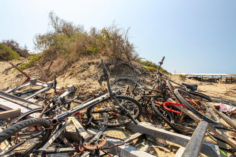 Denizli, Cyprus - August 02, 2018: Sun shining on pile of old rusty discarded bikes laying near beach royalty free stock images