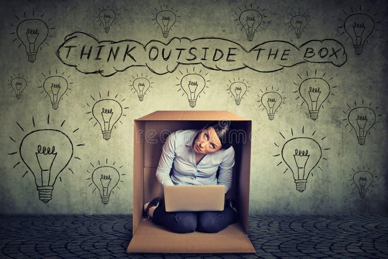 Denk buiten het doosconcept Vrouwenzitting binnen doos gebruiken die aan laptop computer werken royalty-vrije stock afbeelding