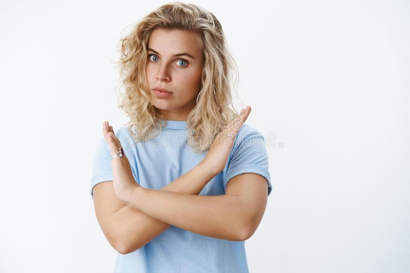 Denk zelfs niet over het Portret van ernstig-kijkt niet bevallen en intens bazig blond wijfje met kort krullend kapsel stock foto