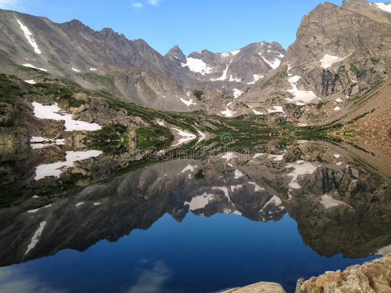 Denken de sneeuw afgedekte bergen in een meer na stock afbeelding