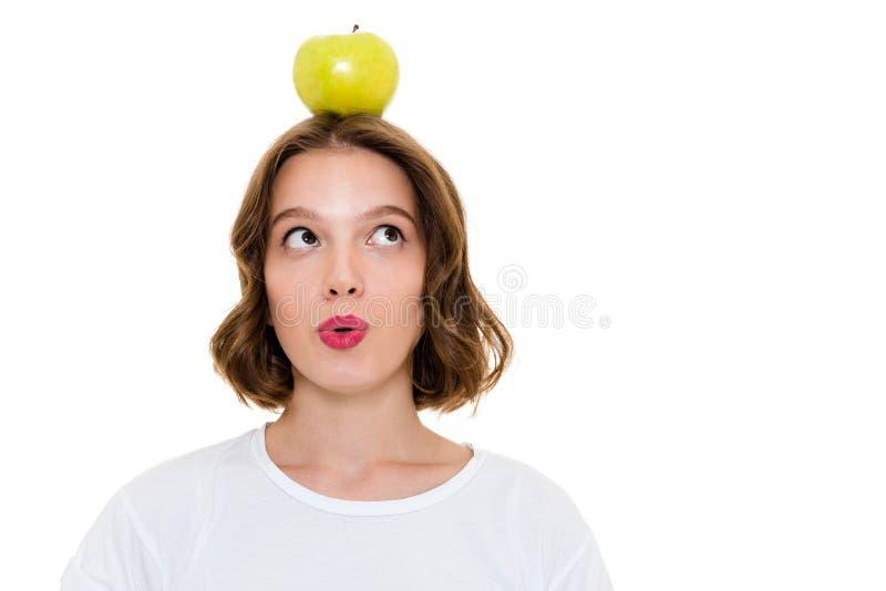 Denken der recht kaukasischen Frau, die Apfel auf Kopf hält lizenzfreie stockfotos