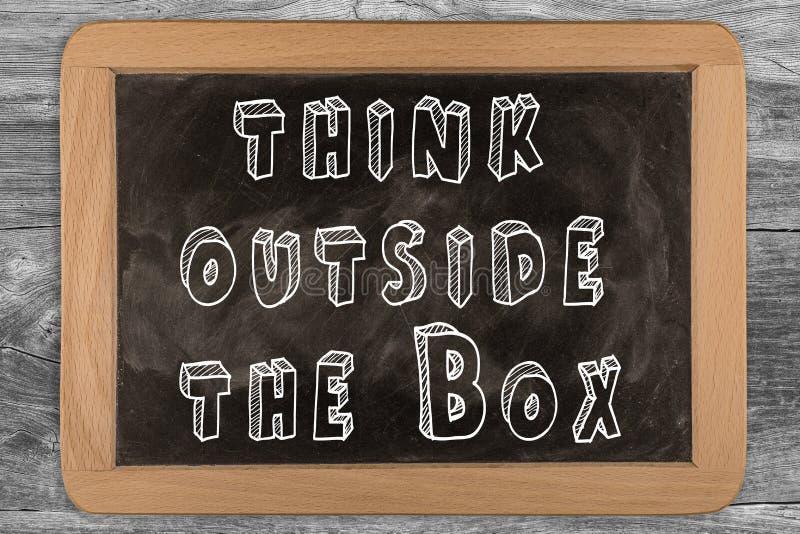Denken Sie außerhalb des Kastens - Tafel mit umrissenem Text lizenzfreie stockfotografie