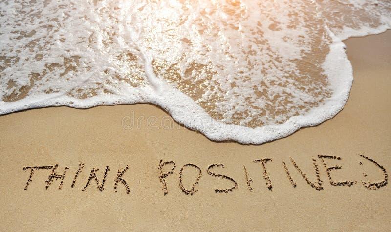 Denken Sie das Positiv, das auf Sandstrand - positives denkendes Konzept geschrieben wird lizenzfreie stockfotos