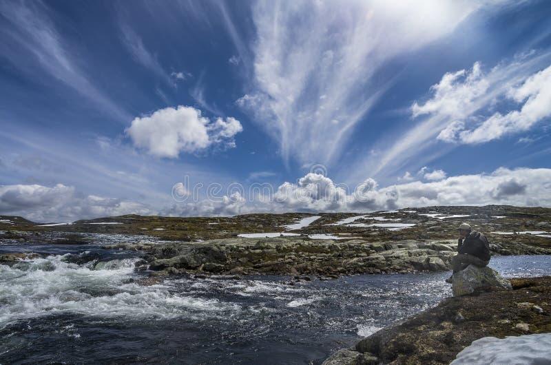 Denken Sie an Fischen Fischer sitzt auf dem Stein in dem Fluss lizenzfreie stockbilder