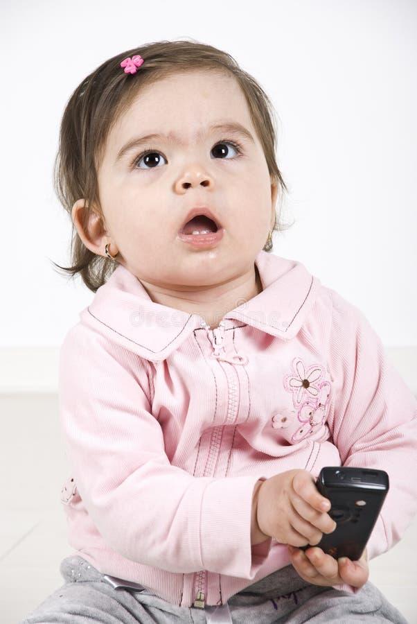Denkend de telefoon van de babyholding mobiel stock afbeeldingen