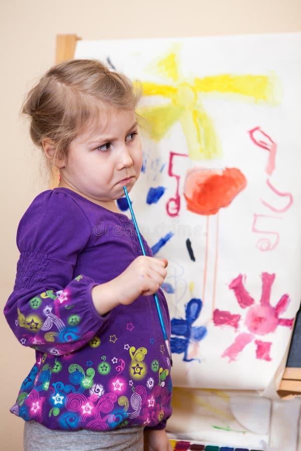 Denkend jong meisje die zich met het schilderen van borstel bevinden stock fotografie