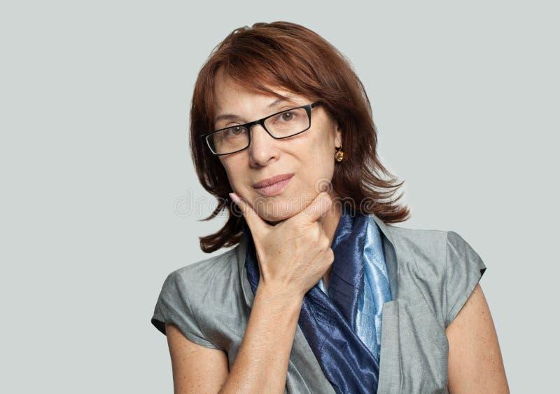 Denkende bedrijfsvrouw in glazen op witte achtergrond stock foto's